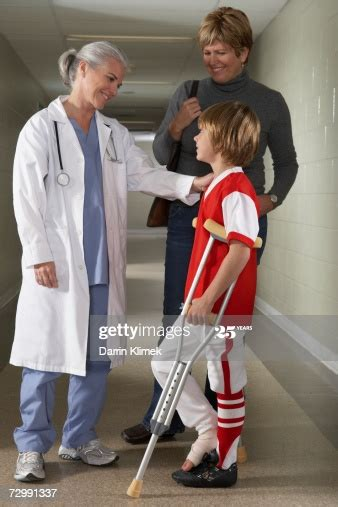 Doctor With Boy Using Crutches Standing In Corridor